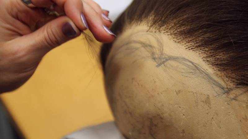 Jurga knots individual strands of hair.